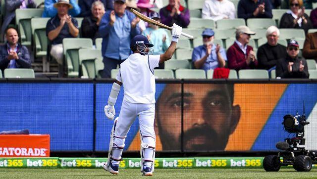 India's Ajinkya Rahane acknowledges the applause as he walks back to the pavilion after his dismissal on the third day of the second cricket Test match between Australia and India at the MCG in Melbourne on December 28, 2020. (Photo by WILLIAM WEST / AFP) / --IMAGE RESTRICTED TO EDITORIAL USE - STRICTLY NO COMMERCIAL USE--