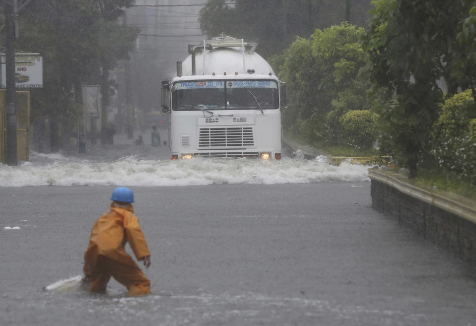 <p>A Filipino worker cleaning garbage looks at a truck navigate a flooded road in suburban Mandaluyong, east of Manila, Philippines, as monsoon downpours intensify while Typhoon Nepartak exits the country on Friday, July 8, 2016. (AP Photo/Aaron Favila) </p>