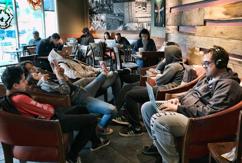 This Thursday, May 24, 2018 file photo shows customers sitting around on cell phones and computers as well as sleeping at a local Starbucks coffee shop in Burbank, Calif. (AP Photo/Richard Vogel)