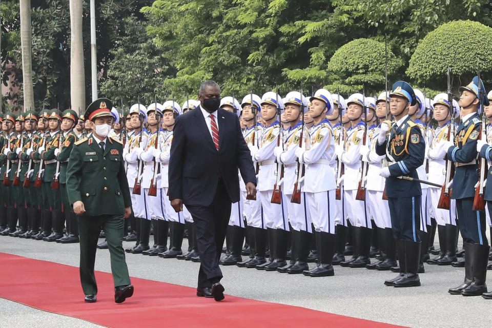 U.S. Secretary of Defense Lloyd Austin with Vietnamese Defense Minister Phan Van Giang, left, inspects an honor guard in Hanoi, Vietnam, Thursday, July 29, 2021. Austin is seeking to bolster ties with Vietnam, one of the Southeast Asian nations embroiled in a territorial rift with China, during a two-day visit. (Nguyen Trong Duc/VNA via AP)