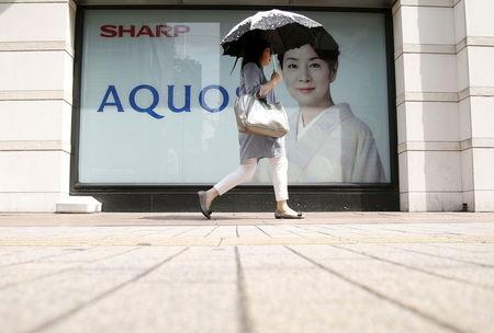 A woman holding her umbrella walks past an advertisement poster for Sharp Corp's Aquos outside an electronics shop in Tokyo