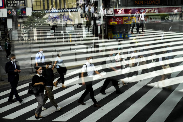Commuters are reflected in a bus window as they cross the street Thursday, July 15, 2021, in Tokyo. (AP Photo/Jae C. Hong)