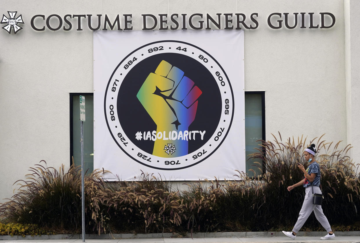 A poster advocating union solidarity in front of a Costume Designers Guild office building.