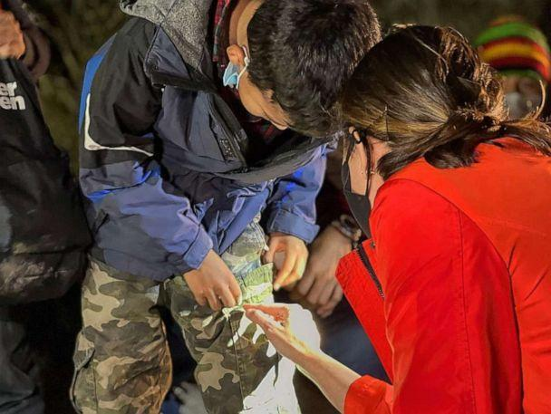 PHOTO: A young boy who was traveling alone while attempting to reach relatives in the United States shows ABC News' Cecilia Vega a relative's phone number written on his pants, at the U.S. Border in March 2021. (Ignacio Torres/ABC News)