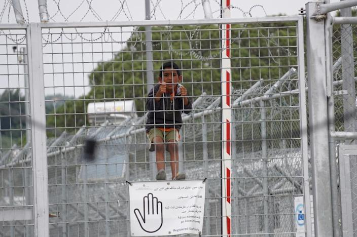 A child looks through the fence at the Moria detention camp for migrants and refugees at the island of Lesbos (AFP Photo/)