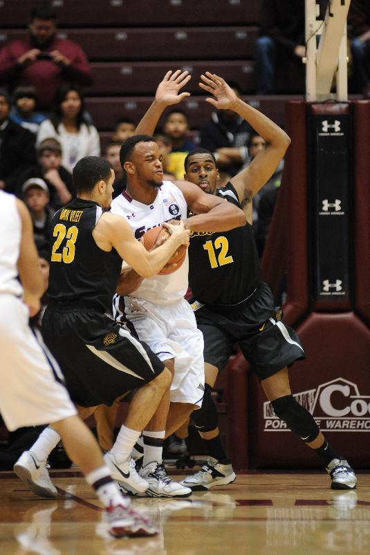 Wichita State's Fred VanVleet (23) and Darius Carter (12) double-team Southern Illinois' Davante Drinkard under the basket during the first period of a Missouri Valley Conference NCAA college basketball game in Carbondale, Ill., Thursday, Jan. 2, 2014. (AP Photo/Stephen Lance Dennee)