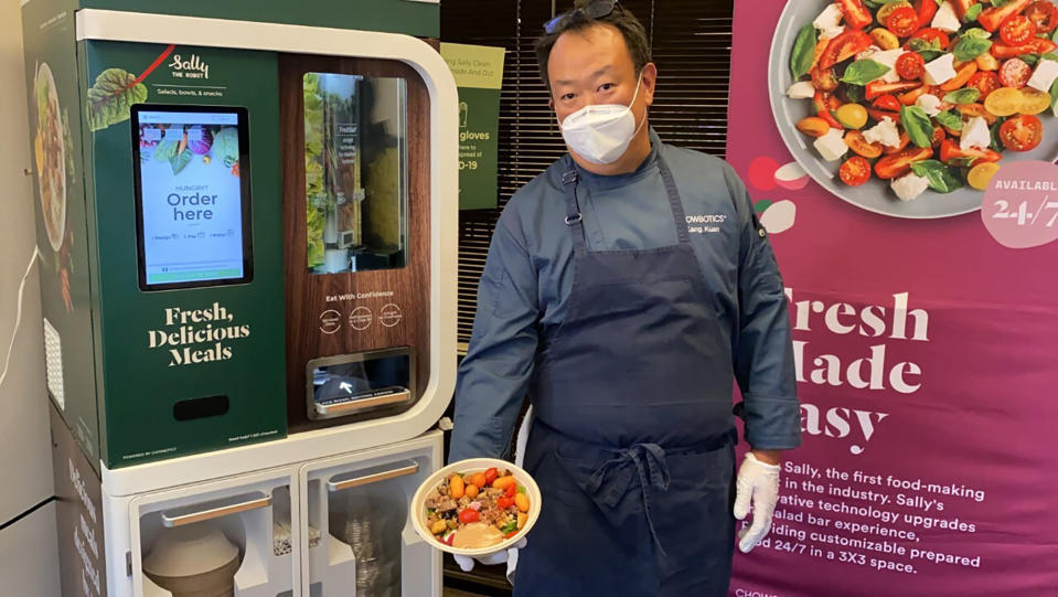 FILE - In this June 23, 2020 file photo, Kang Kuan, vice president of culinary at Chowbotics, holds a custom salad made by his company's robotic salad-making kiosk at the company's headquarters in Hayward, Calif. DoorDash is buying the automated food prep company to expand its fresh meal offerings. San Francisco-based DoorDash announced the acquisition Monday, Feb. 8, 2021. (AP Photo/Terry Chea, File)