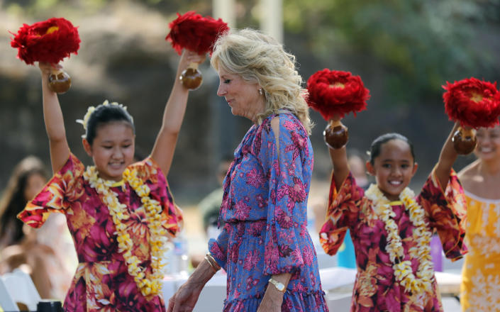 First lady Jill Biden walks past hula dancers with Ka Pa Nani o Lilinoe during a barbecue at the gym and recreation area of Makalapa Crater at Joint Base Pearl Harbor-Hickam, Hawaii, Sunday, July 25, 2021. The first lady met with more than 75 members of the military and their families before departing Hawaii for Washington on Sunday afternoon. (Jamm Aquino/Honolulu Star-Advertiser via AP)