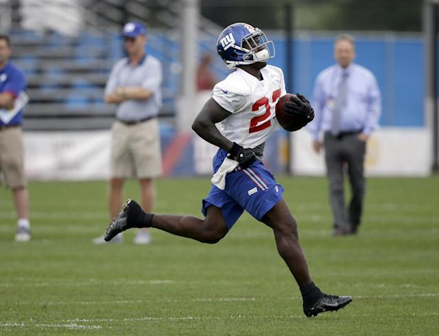 FILE - In this July 24, 2014, file photo, New York Giants running back David Wilson runs the ball during NFL football camp in East Rutherford, N.J. Two weeks after ending his NFL career due to a neck injury, former Giants' Wilson is turning to track and field. The 23-year-old Wilson, who competed in the triple jump during high school and at Virginia Tech, intends to train in the event with an eye on making the United States team for the 2016 Rio Olympics. (AP Photo/Seth Wenig, File)
