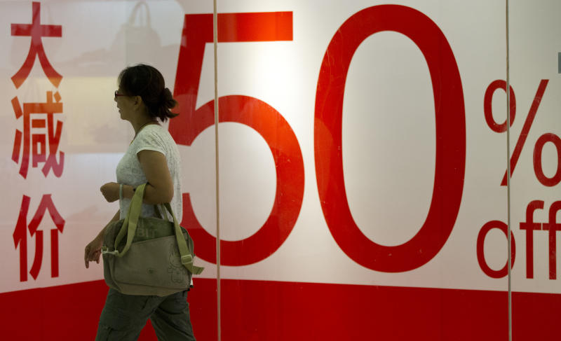 A woman walks past a promotional advertisement in a shopping mall in central Beijing, China, Thursday, Aug. 9, 2012. China's inflation rate fell further in July, giving the government more room to stimulate growth amid mixed signals about whether the world's second-largest economy is recovering from a painful slowdown. (AP Photo/Alexander F. Yuan)