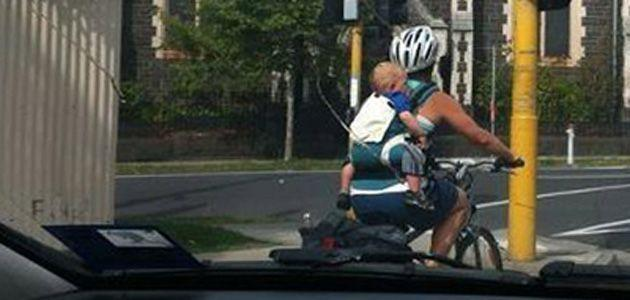 Cyclist rides with baby strapped to her back. Photo: Herald Sun