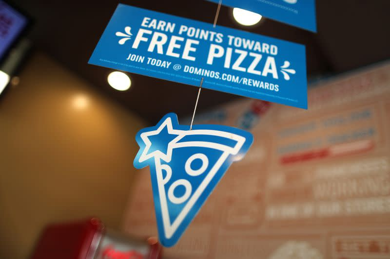 A Domino's Pizza sign hangs in a restaurant in Los Angeles