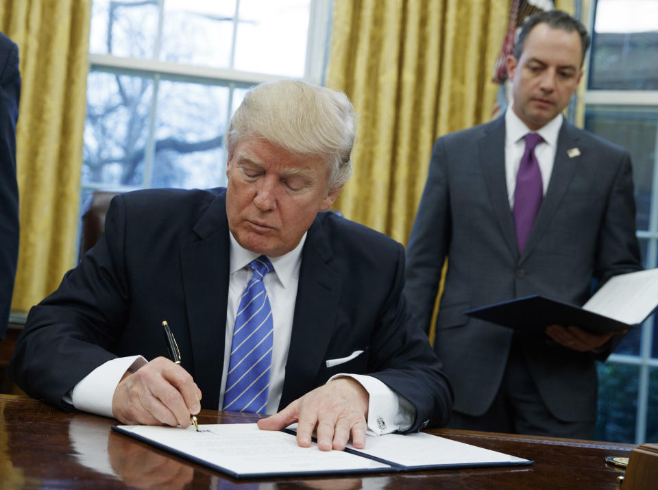 FILE - In this Jan. 23, 2017, file photo, U.S. President Donald Trump signs an executive order to withdraw the U.S. from the 12-nation Trans-Pacific Partnership (TPP) trade pact agreed to under the Obama administration in the Oval Office of the White House in Washington. Members of a Pacific Rim trade initiative rejected by Trump are to hold working-level talks Wednesday, July 12, 2017 in the Japanese mountain resort town of Hakone, west of Tokyo. The three-day meeting among envoys from the 11 remaining members of the TPP follows a breakthrough last week on a Japan-European Union trade deal seen as a repudiation of the U.S. moves to pull back from such arrangements. (AP Photo/Evan Vucci, File)