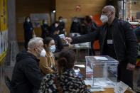 A man working at a polling station set up in a market, is taken the temperature during the regional Catalan election in Barcelona, Spain, Sunday, Feb. 14, 2021. Over five million voters are called to the polls on Sunday in Spain's northeast Catalonia for an election that will measure the impact of the coronavirus pandemic on the restive region's secessionist movement. (AP Photo/Emilio Morenatti)