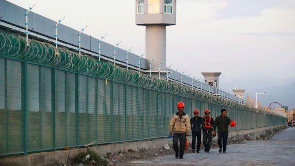 PHOTO: Workers walk by the perimeter fence of what is officially known as a vocational skills education centre in Dabancheng in Xinjiang Uighur Autonomous Region, China Sept. 4, 2018. (Thomas Peter/Reuters, FILE)