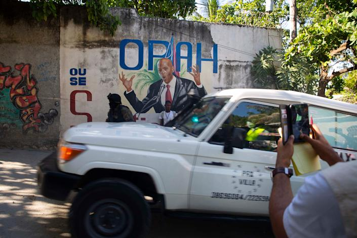An ambulance carrying the body of Haiti's President Jovenel Moise drives past a mural featuring him near the leader's residence where he was killed by gunmen in the early morning in Port-au-Prince, Haiti, Wednesday, July 7, 2021. Claude Joseph, the interim prime minister, confirmed the killing and said the police and military were in control of security in Haiti.