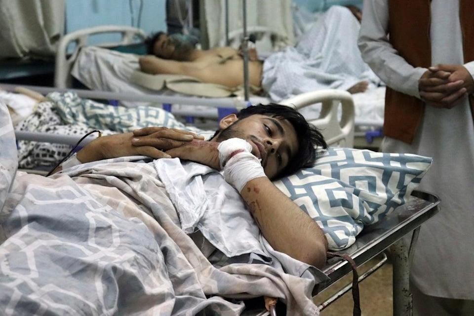 An Afghan man lies on a bed at a hospital after he was wounded in the deadly attacks outside the airport in Kabul   (AP)