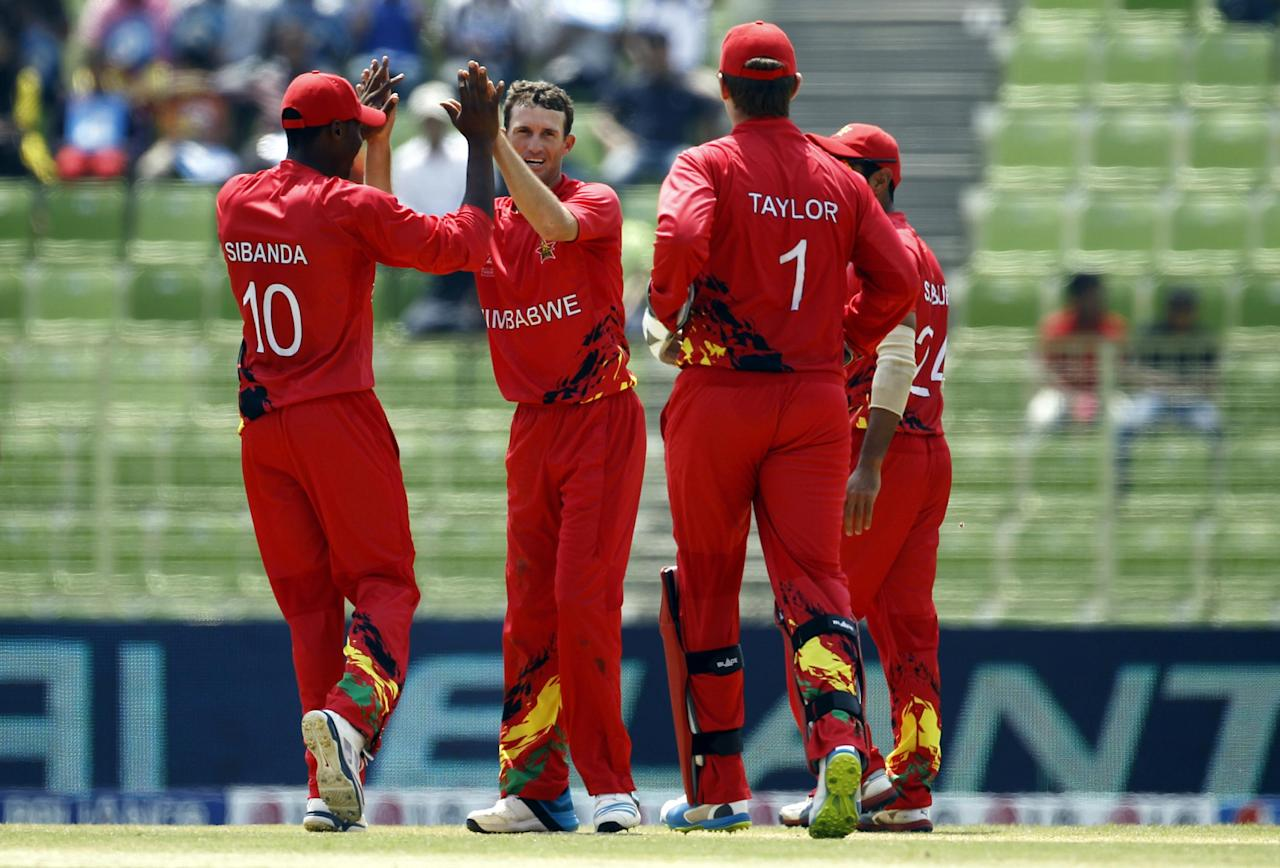 Zimbabwe's Sean Williams, second left, celebrates with his teammates the dismissal of United Arab Emirates' captain Khurram Khan during their ICC Twenty20 Cricket World Cup match in Sylhet, Bangladesh, Friday, March 21, 2014. (AP Photo/A.M. Ahad)