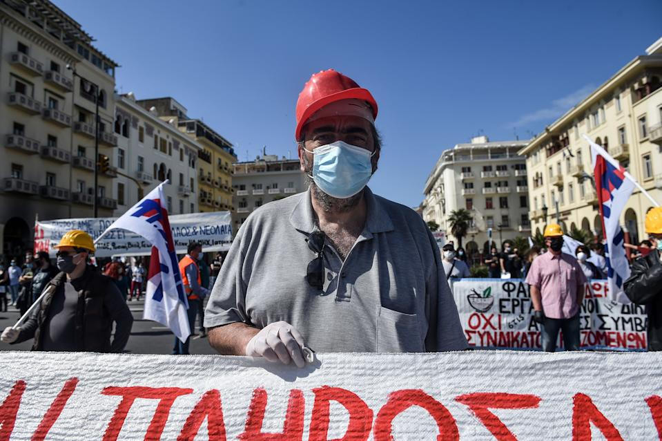 A member of the Greek Labour Union (PAME), wearing a protective mask against the spread of the novel coronavirus, COVID-19,  protest during the Labour Day demonstration in Thessaloniki on May 1, 2020, as the Greek government asked unions to delay public rallies by more than a week, but leading union GSEE called for a general strike to coincide with May Day. - Workers were forced to scale back May Day rallies around the world on May 1, 2020, because of coronavirus lockdowns, although some pushed on with online events and others hit the streets in face masks. (Photo by Sakis MITROLIDIS / AFP) (Photo by SAKIS MITROLIDIS/AFP via Getty Images)