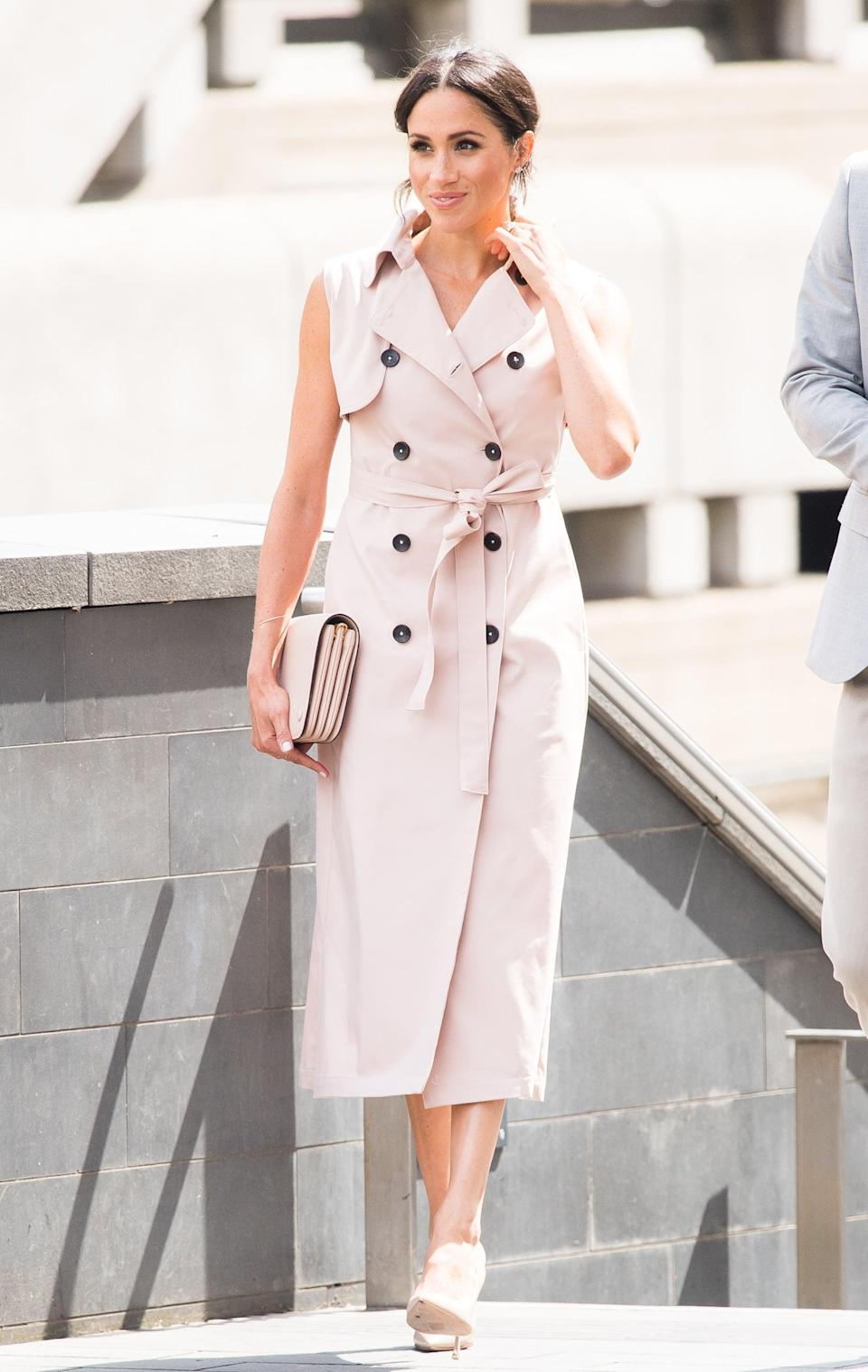 """<p>A belted trench-coat dress is one of Meghan's go-to looks. In July 2018, the duchess wore <a href=""""https://www.popsugar.com/fashion/Meghan-Markle-Pink-Trench-Dress-House-Nonie-45055695"""" class=""""link rapid-noclick-resp"""" rel=""""nofollow noopener"""" target=""""_blank"""" data-ylk=""""slk:a pink trench dress by Canadian designer Nonie"""">a pink trench dress by Canadian designer Nonie</a> to visit The Nelson Mandela Centenary Exhibition at Southbank Centre in July 2018.</p>"""