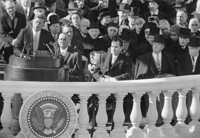 FILE - In this Jan. 20, 1961, black and white file photo,President John F. Kennedy gives his inaugural address at the Capitol in Washington after taking the oath of office. Listening in the front row, from left, are, incoming Vice President Lyndon Johnson, outgoing Vice president and Kennedy's defeated presidential opponent Richard M Nixon, Sen John Sparkman, D- Ala., and former President Harry Truman. (AP Photo, File)