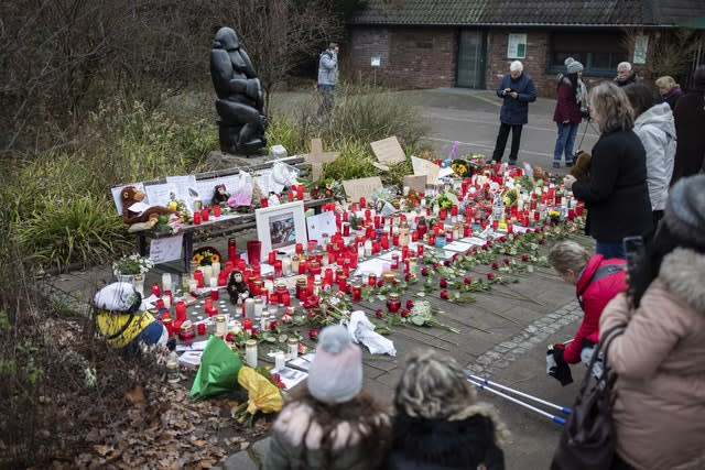 A woman lights a candle at the main entrance of the zoo in Krefeld, Germany