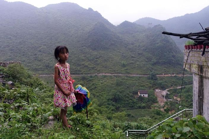 Meng Yiping, who lives with her grandparents, stands near her home in Longfu Township, in southern China's Guangxi province, on June 19, 2015 (AFP Photo/Johannes Eisele)