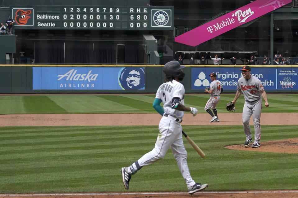 Baltimore Orioles starting pitcher John Means, right, starts to celebrate after Seattle Mariners' J.P. Crawford, foreground, lined out for the final out in a no-hitter by Means in a baseball game Wednesday, May 5, 2021, in Seattle. The Orioles won 6-0. (AP Photo/Ted S. Warren)