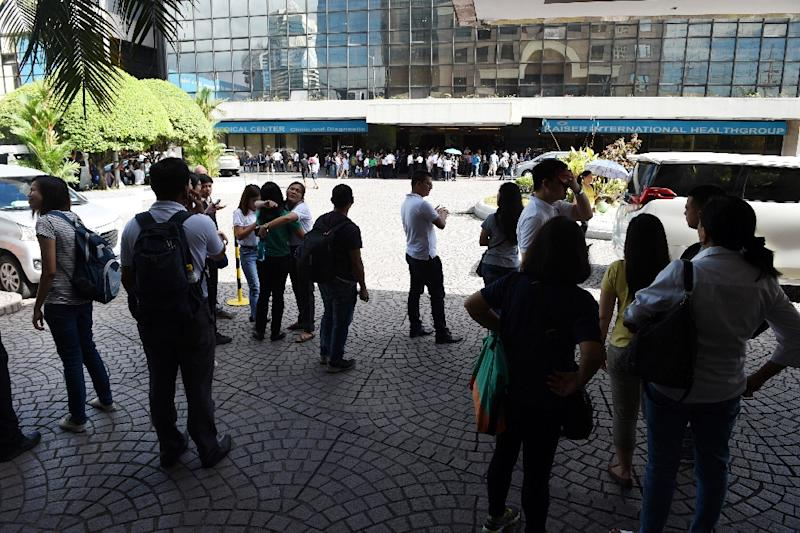 Office workers stand on the grounds of an office building in the financial district of Makati in Manila on April 8, 2017, after a 5.7 magnitude earthquake struck