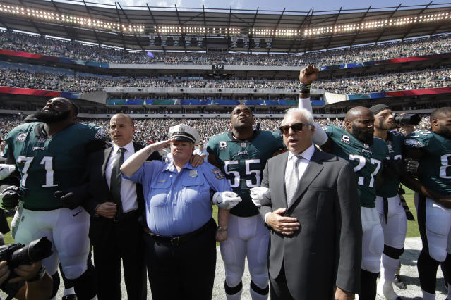 <p>Philadelphia Eagles players and owners Jeffrey Lurie stand for the national anthem before an NFL football game against the New York Giants, Sunday, Sept. 24, 2017, in Philadelphia. Eagles' Malcolm Jenkins is seen raising his fist next to Lurie. (AP Photo/Matt Rourke) </p>