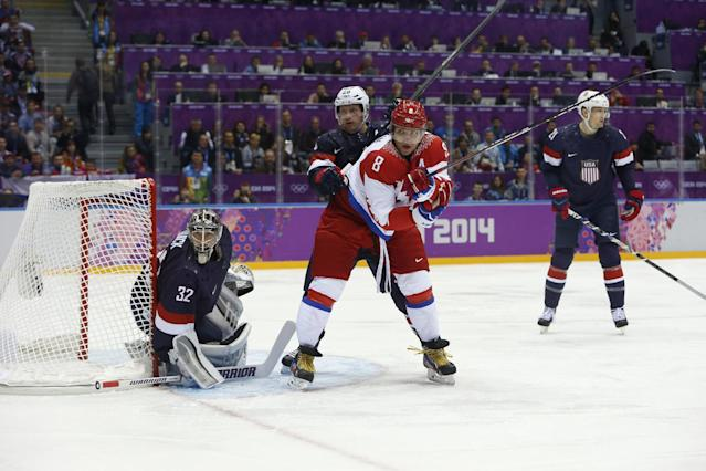 USA defenseman Ryan Suter and Russia forward Alexander Ovechkin jockey for position as USA goaltender Jonathan Quick defends the goal in the first period of a men's ice hockey game at the 2014 Winter Olympics, Saturday, Feb. 15, 2014, in Sochi, Russia. (AP Photo/Mark Humphrey)