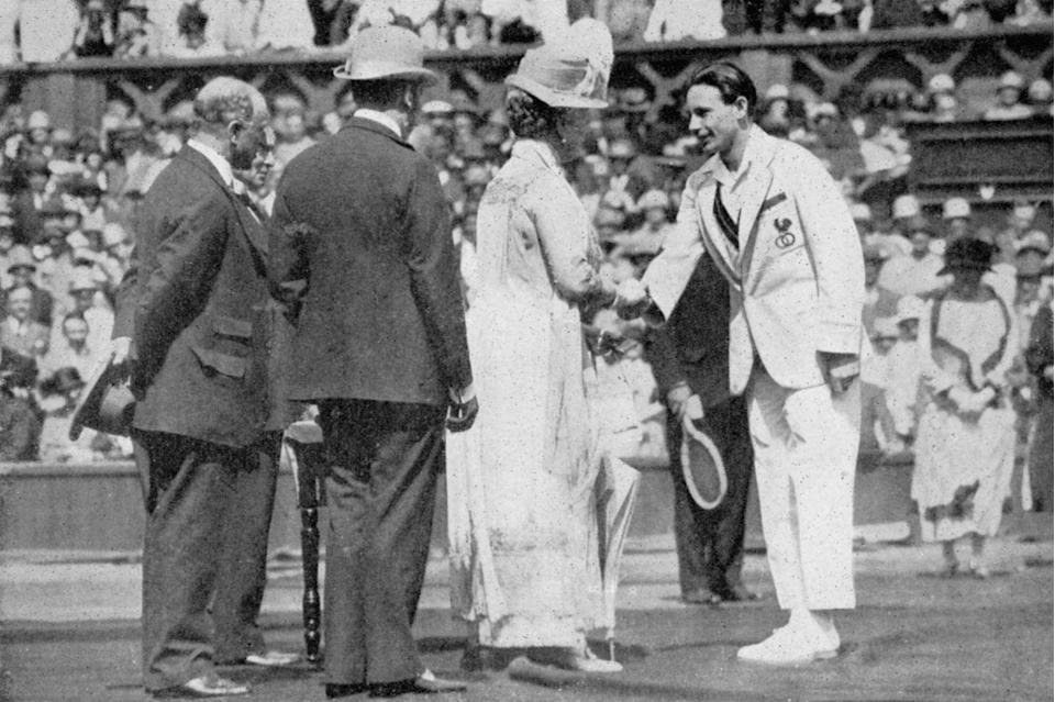 <p>Jean Boratra receives his medal from Queen Mary.</p>