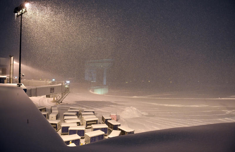 Airline baggage carts sit on the tarmac as crews prepare to remove snow at the Albany International Airport in Colonie, N.Y., Sunday, Jan. 20, 2019. (AP Photo/Hans Pennink)