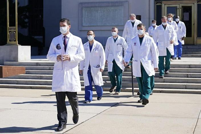 "Dr. Sean Conley, physician to President Trump, is followed by a team of doctors for a briefing with reporters at Walter Reed National Military Medical Center on Saturday. <span class=""copyright"">(Susan Walsh / Associated Press)</span>"