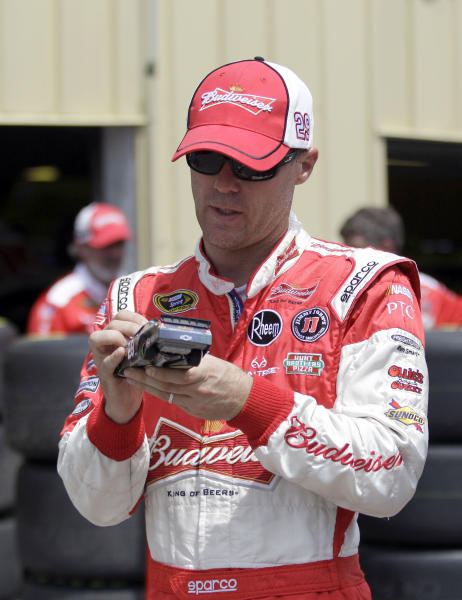 NASCAR driver Kevin Harvick signs a car for a fan after practice for the NASCAR New Hampshire Sprint Cup Series Camping World RV Sales 301 auto race, Friday, July 12, 2013 in Loudon, N.H. (AP Photo/Mary Schwalm)