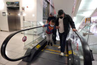 Yancarlos Amaya, 5, front left, a migrant from Honduras, leaps off an escalator while holding the hand of family friend Dimas Barahona, front right, at Baltimore-Washington International Thurgood Marshall Airport, in Linthicum, Md., Wednesday, March 24, 2021. Yancarlos and his mother, Celestina Ramirez, were reunited with Ramirez's brother, Marco Ramirez, when they arrived in Baltimore. (AP Photo/Julio Cortez)