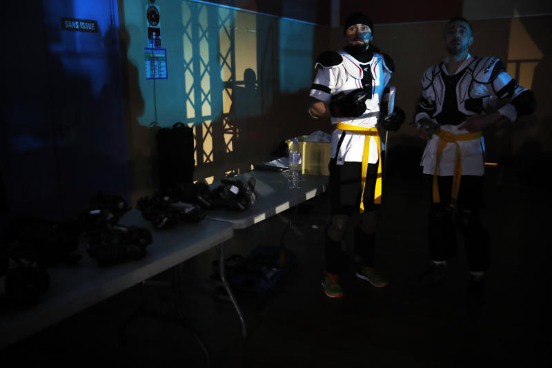 In this Sunday, Feb. 10, 2019, photo, Steven Hildevert, left, and Stephane Devallois prepare to compete during the national lightsabers tournament in Beaumont-sur-Oise, north of Paris. In France, lightsaber fighting is an official sport, recognized as such by the French Fencing Federation. The sport's practitioners, many but not all of the fans of 'Stars Wars,' have had to build the discipline's competition rules almost from scratch. (AP Photo/Christophe Ena)