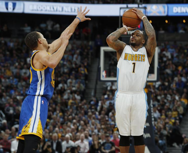 Denver Nuggets guard Jameer Nelson, right, takes a three-point shot over Golden State Warriors guard Stephen Curry in the second half of an NBA basketball game Monday, Feb. 13, 201, in Denver. The Nuggets won 132-110. (AP Photo/David Zalubowski)