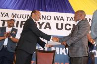 Tanzania's re-elected President John Pombe Magufuli receives his winning certificate from the Chairman of the National Electoral Commission (NEC) Semistocles Kaijage at the Commission (NEC) headquarters within the Njedengwa suburb in Dodoma