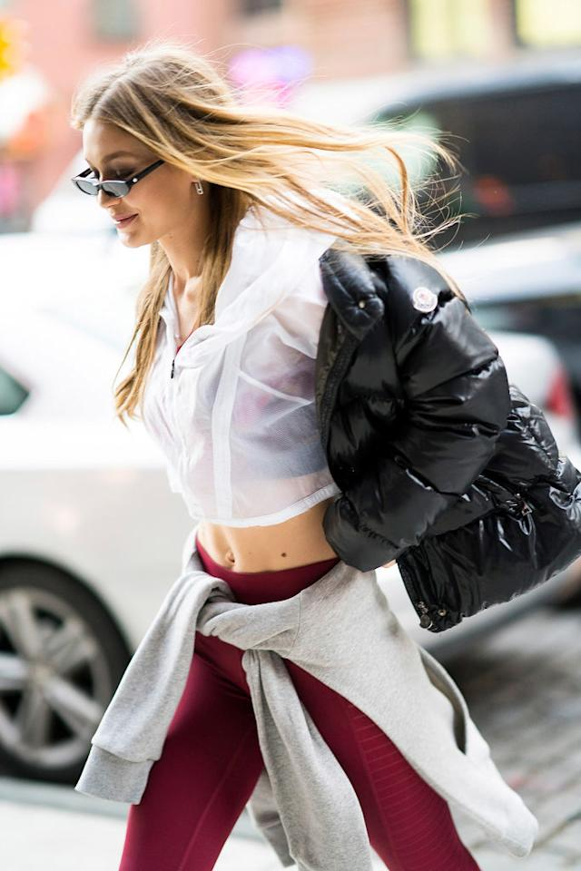 <p>The older Hadid makes a puffer look trendy, layering the down Moncler jacket over an athleisure look. (Photo: Getty Images) </p>