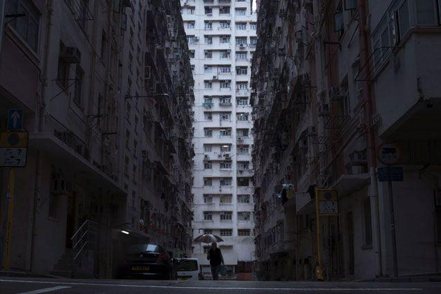 A a man walks in front of a residential and commercial building, centre, where the