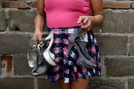 Ximena, 26, an indigenous Zapotec transgender woman also know as Muxe, holds her muddy shoes as she poses for a photo inside her house destroyed after an earthquake that struck on the southern coast of Mexico late on Thursday, in Juchitan, Mexico, September 10, 2017. REUTERS/Edgard Garrido
