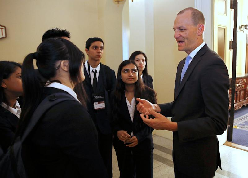 Assemblyman Kevin McCarty, D-Sacramento, right, talks with a group of high school students after his news conference concerning a proposed package of bills dealing with the recent college admissions scandal, Thursday, March 28, 2019, in Sacramento, Calif.