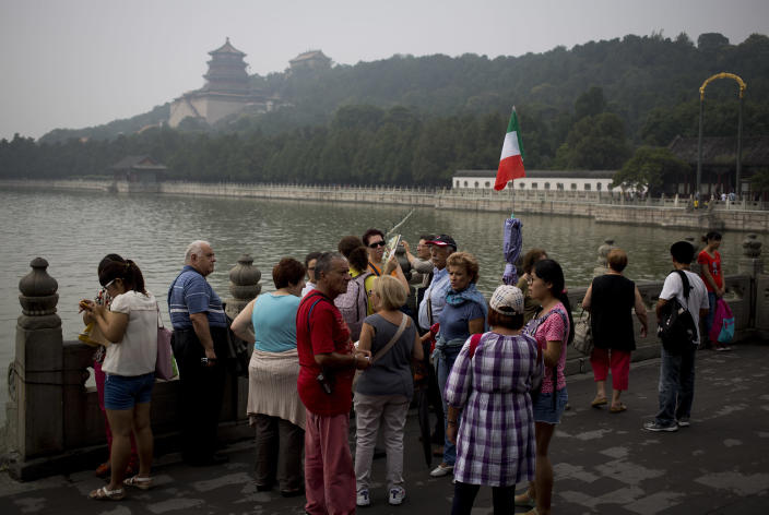 "In this Wednesday, Aug. 28, 2013 photo, a group of Italian tourists visit the Summer Palace with the Buddhist towers in the background in Beijing. China's tourism industry has grown at a fast pace since the country began free market-style economic reforms three decades ago. However, it's latest tourism slogan ""Beautiful China"" has been derided as particularly inept at a time when record-busting smog has drawn attention to the environmental and health costs of China's unfettered industrialization. Some point to unsophisticated marketing as an explanation. (AP Photo/Andy Wong)"