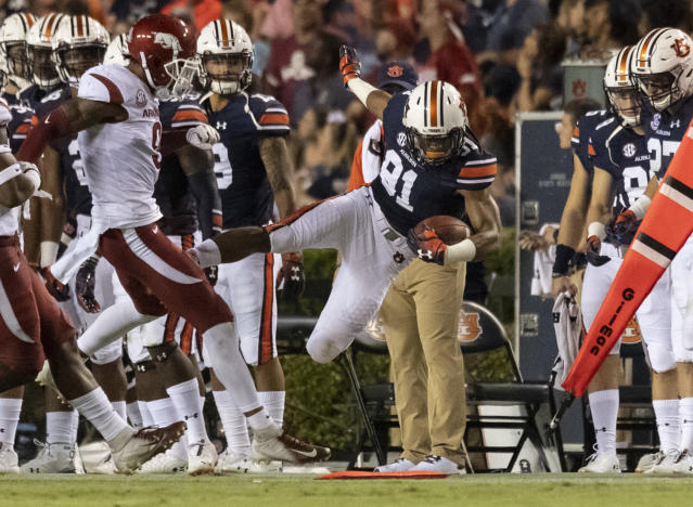 Auburn wide receiver Darius Slayton (81) flies out of bound on a hit from Arkansas defensive back Santos Ramirez (9) at the end of a pass play during the first half of an NCAA college football game, Saturday, Sept. 22, 2018, in Auburn, Ala. (AP Photo/Vasha Hunt)