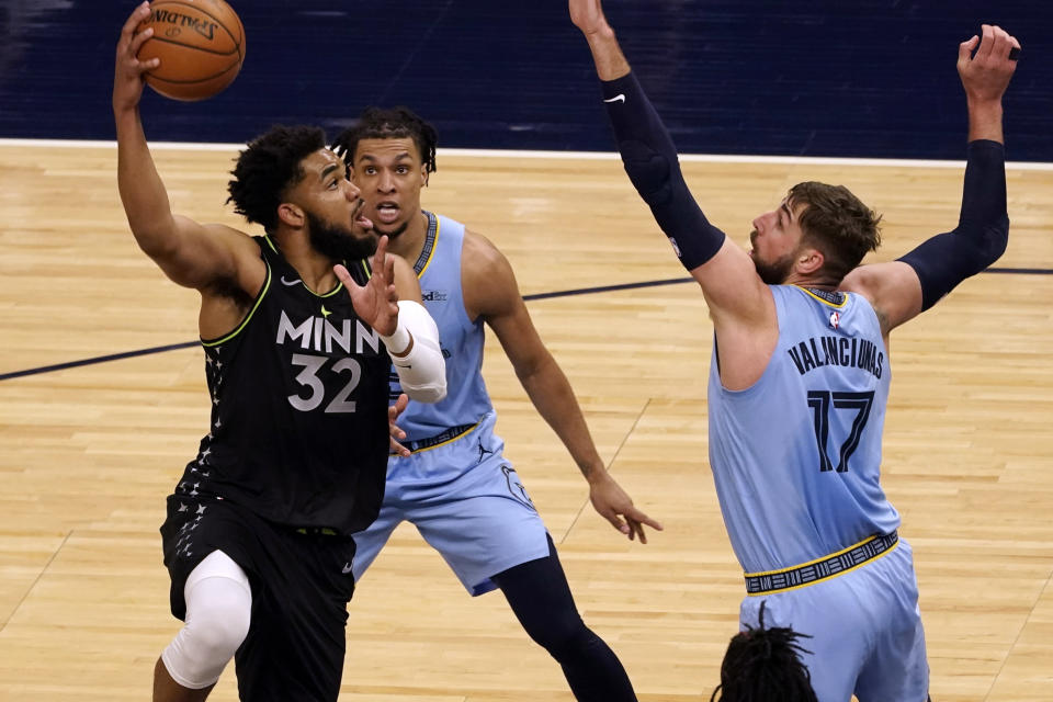 Minnesota Timberwolves' Karl-Anthony Towns (32) shoots as Memphis Grizzlies' Jonas Valanciunas (17) defends in the first half of an NBA basketball game Wednesday, May 5, 2021, in Minneapolis. (AP Photo/Jim Mone)