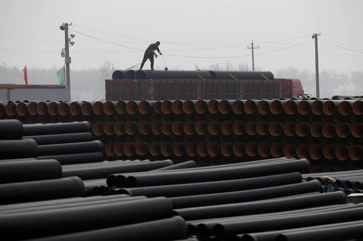 A worker packs pipelines onto a truck at a local plastic pipe factory in Donghegang village on the outskirts of Xiongxian county