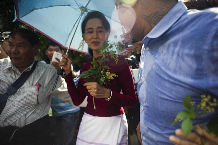 Myanmar opposition leader Aung San Suu Kyi (C) accepts flowers from her supporters as she visits a polling station in Kawhmu township, Yangon on November 8, 2015 (AFP Photo/Ye Aung Thu)