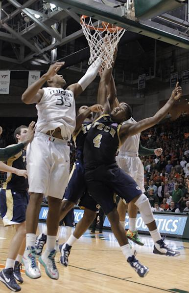 Georgia Tech's Marcus Georges-Hunt, center background, and teammate Robert Carter (4) try to tip in a missed shot by Georges-Hunt at the buzzer, as Miami's Kenny Kadji (35) defends during the second half of an NCAA college basketball game in Coral Gables, Fla., Wednesday, March 6, 2013. The tip went in, and Georgia Tech won 71-69. (AP Photo/Luis M. Alvarez)