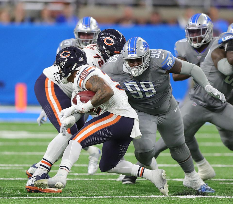 Detroit Lions defensive tackle John Atkins (99) tackles Chicago Bears running back David Montgomery during the first half Thursday, Nov. 28, 2019 at Ford Field.